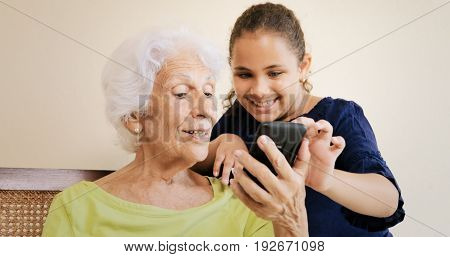 Girl Helps Grandmother Using Mobile Phone And Technology