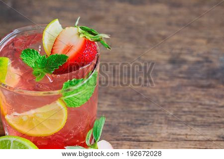 Strawberry lemon lime mojito in clear glass on rustic wood table. Homemade beverage strawberry soda ingredients with strawberry lemon or lime and mint leaf. Homemade infused water close up concept. Wood plank background for summer design.