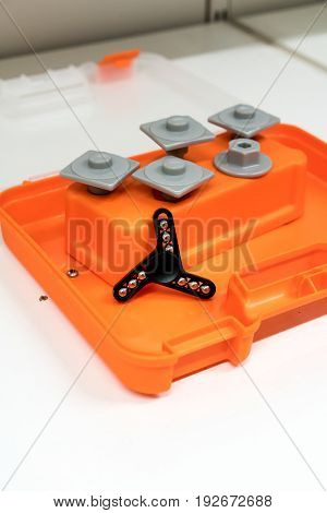 Black aluminum hand spinner with metal balls inside on kid's orange color toolbox. Aluminum fidget spinner goes round with kids for concept