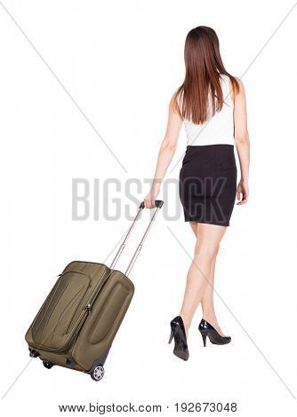 back view of walking  woman  with green suitcase. beautiful brunette girl in motion.  Rear view people collection. Isolated over white background. girl in a striped dress goes ahead with travel bag