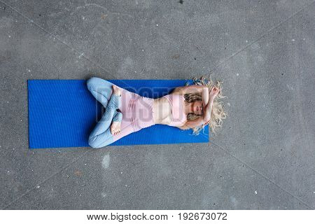 Young slim blond woman making yoga exercises on the street