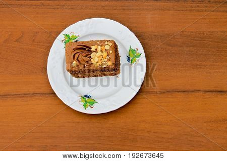 Piece of cake with nuts on plate on the wooden table. Top view
