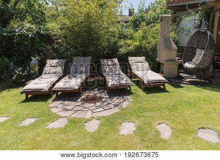 Garden sunbeds on green grass bamboo fence background. Garden bed for sunbathing and rest. Four garden bed.