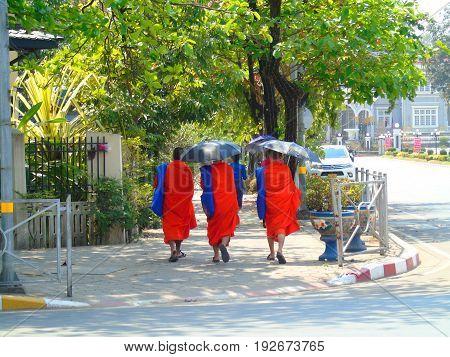 Monks with umbrellas in city Vientiane, Laos