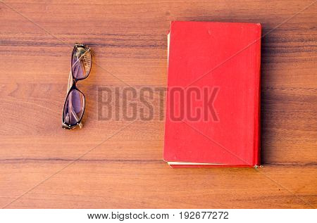 Close old book with glasses on the wooden desk