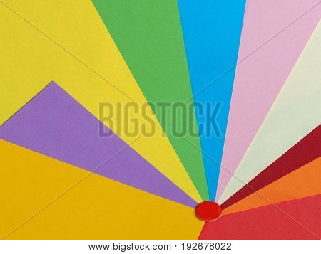Colored paper background in a fan pattern with a red dot