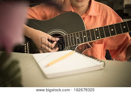 girl student compose song in notebook and playing guitar in school