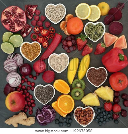 Paleolithic diet food of fresh fruit, vegetables, nuts and seeds on slate background. High in antioxidants, vitamins, anthocyanins and dietary fiber.