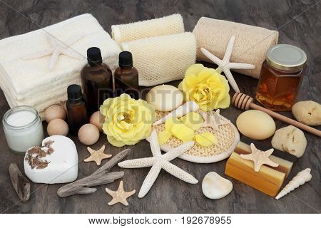 Natural spa and body scrub cleansing beauty products with yellow rose flowers, aromatherapy oil, moisturising cream, bath bombs, honey and shells.