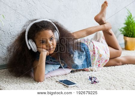 Bored African girl at home listening to music in big white headphones