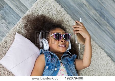 cute African girl at home listening to music in big white headphones Lies on the floor