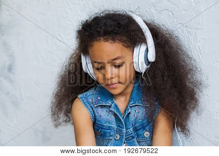 Pretty African girl at home listening to music in big white headphones