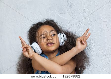 cute African girl listening to music in big white headphones With crossed arms