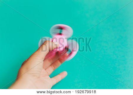 Fidget spinner, spinning in hand on trendy pastel blue background.