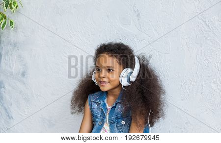 cute African girl listening to music in big white headphones