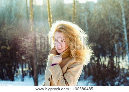 Smiling girl in the wood winter at sunset. Beautiful happy young woman wearing coat with curly blonde hair posing in winter forest at sunny evening. Caucasian female model looking away.