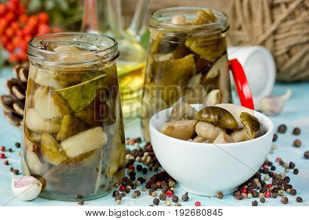 Forest mushrooms pickled in jar on kitchen table autumnal preserves preparing