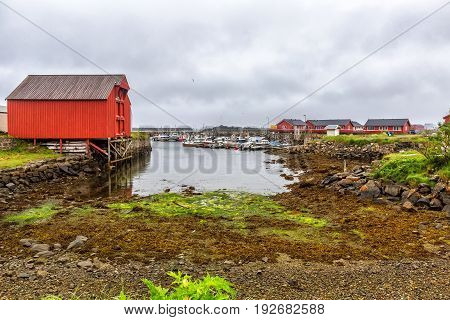 Ships, Motorboats And Wooden Warehouse In A Small  Harbor.
