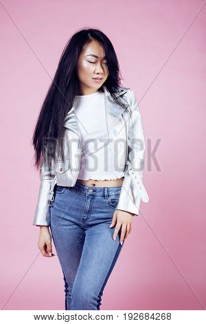 young pretty smiling asian korean girl wearing modern fashion clothers on pink background, lifestyle people concept close up