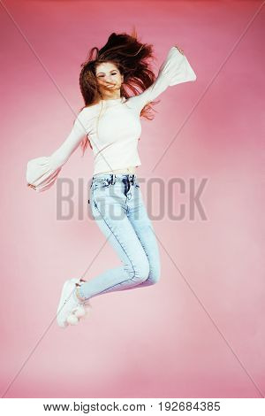 young pretty teenage redhair girl jumping cheerful isolated on pink background, lifestyle people concept close up