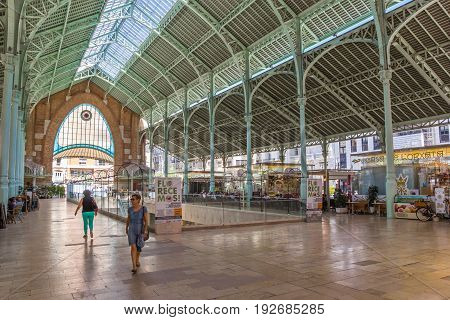 VALENCIA, SPAIN - JUNE 12, 2017: People shopping at the Mercado Colon market hall in Valencia, Spain