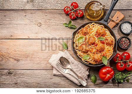 Spaghetti pasta with meatballs and tomato sauce in cast iron pan over wooden background, top view