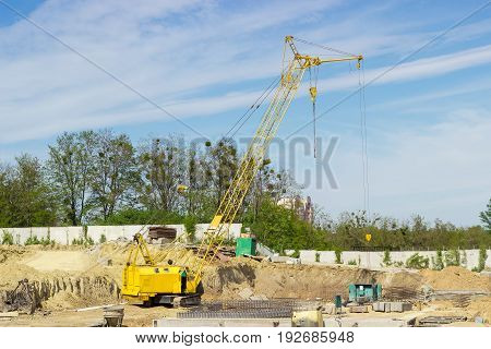 Yellow crawler self-propelled crane with latticed boom on the construction site during construction of the reinforced concrete basement of a building