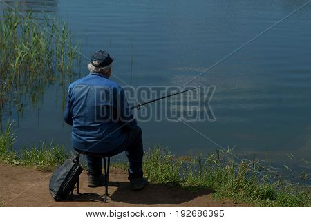Fisherman With Fishing Rod Catching Fish, Sitting Riverside.