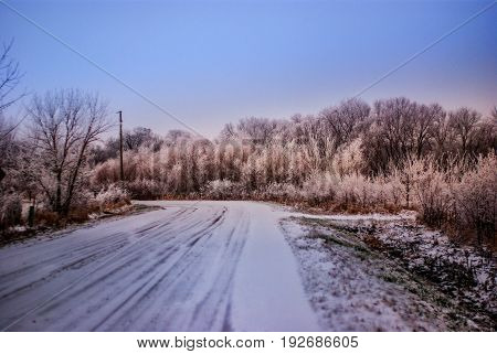 A snow covered gravel road in a rural area