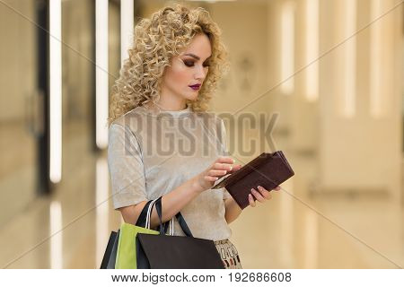 Portrait Of Thoughtful Beautiful Person Holding Open Wallet With Pensive Expression In Shopping Cent