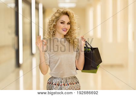Happy Young Girl With Shopping Bags Smiling And Showing Ok In Mall.