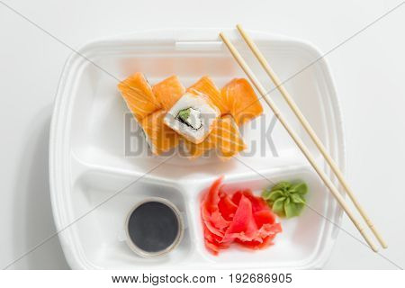 Roll With Chopsticks, Rolls, Sushi. Chopsticks, Ginger, Soy Sauce In Container Delivery On White Bac