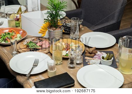 Friendly Dinner. Group Of People Having Dinner Together While Sitting At The Wooden Table