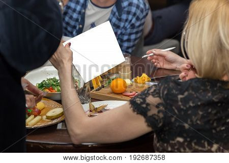 People Having Dinner Together While Sitting At The Wooden Table. Female Hand Holding White Paper