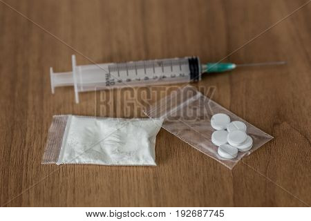 Spoon, Plastic Packet With Cocaine And Syringe On The Wooden Table.