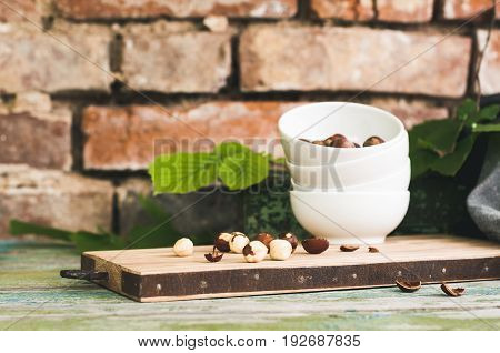 White Cup With A Filbert On A Chopping Board Against The Background Of A Birch Wall