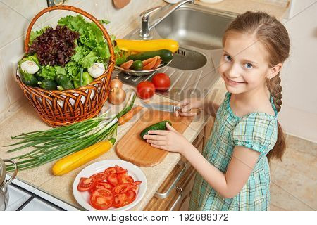 girl chopping cucumber in kitchen, vegetables and fresh fruits in basket, healthy nutrition concept