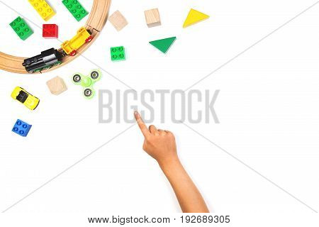 Child pointing finger to colorful toys. Fidget spinner, cars, toy train, bricks and blocks on white background