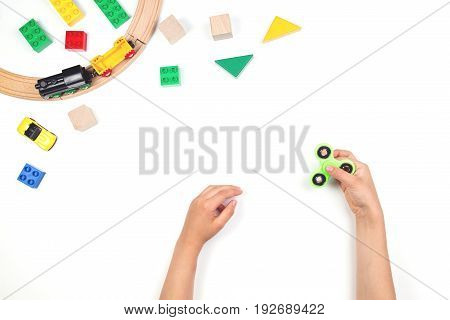 Kids hands playing with fidget spinner toy. Many colorful toys on white background. Top view