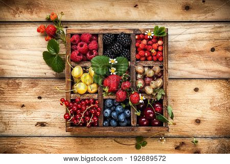 Mix of fresh berries with leaves in vintage wooden box on rustic wooden background. Top view. Raw healthy food. Assorted berries.