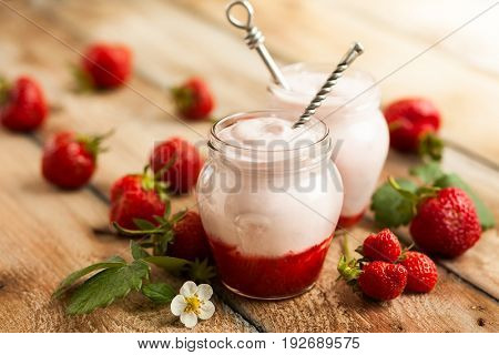 Delicious strawberry yogurt in jars surrounded by fresh berries on the rustic wooden table. Concept of healthy breakfast with strawberry and yogurt
