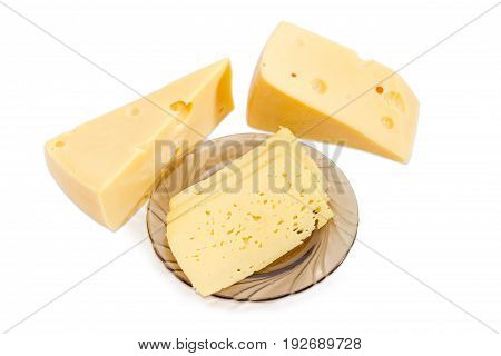Semi-hard cheese cut into thin rectangular slices on the dark glass saucer and two pieces of the Swiss-type cheese beside on a light background