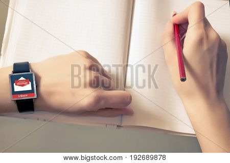 An e-mail online on a smart watch. A smart clock on a woman's hand. Message online icon. Planning concept.