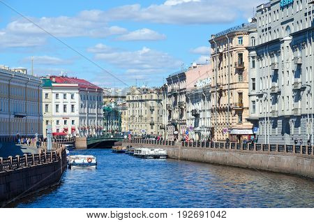 SAINT PETERSBURG RUSSIA - MAY 3 2017: Excursion boats on Moika River near Green Bridge. Unknown people walk along street St. Petersburg Russia