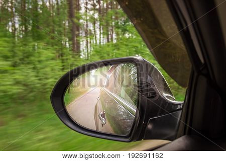 A view in the side view mirror. Mirror rear car. Reflection of the road in motion