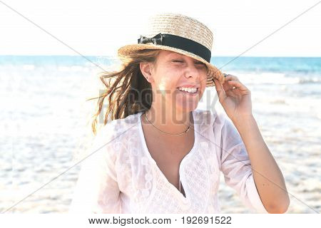 Young woman in a straw hat, fervently laughing against the background of the sea, a large portrait in retro style. The concept of a young and healthy lifestyle.