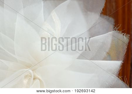 Closeup of a white chiffon bow over a brown wooden surface