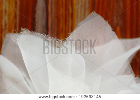 Closeup of white chiffon fabric against brown wooden texture