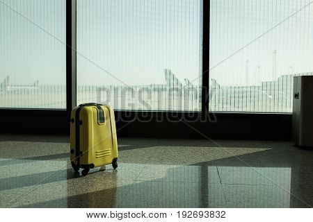 Suitcases in airport departure lounge, airplane in background, summer vacation concept, traveler suitcases in airport terminal waiting area, empty hall interior with large windows, focus on suitcases