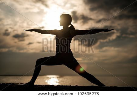 Yoga outdoors. Sporty fit caucasian woman doing Ashtanga Vinyasa Yoga asana Virabhadrasana 2 Warrior pose posture on sea beach. Silhouette view